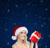Beautiful woman in Christmas cap hands present, snowfall background