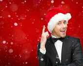 Half-length portrait of businessman wearing Santa Claus cap who attention gestures, isolated on white. Concept of holidays and Christmas