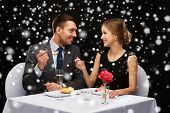 food, christmas, holidays and people concept - smiling couple eating dessert at restaurant over black snowy background