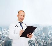 medicine, profession, urrban life and healthcare concept - smiling male doctor with clipboard and stethoscope writing prescription over city background