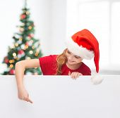 christmas, holidays and advertisement concept - happy girl in santa helper hat pointing finger on blank white board over living room with christmas tree background