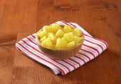 bowl of pineapple pieces on striped dishtowel