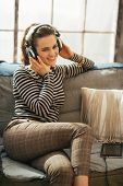 Happy Young Woman Sitting On Sofa In Loft Apartment And Listening Music In Headphones