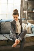 image of legs apart  - Thoughtful business woman in loft apartment checking tired legs - JPG