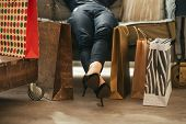 Closeup On Relaxed Young Woman With Shopping Bags In Loft Apartm