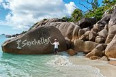 Enthusiastic Man Standing Beside Boulder Formation on Seychelles Beach