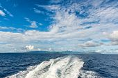 Seascape with the wake of a speeding motorboat leaving a trail or turbulent white water through the calm blue ocean