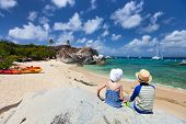 pic of virginity  - Back view of two kids sitting on granite boulder and enjoying beautiful scenery of The Baths beach area major tourist attraction at Virgin Gorda - JPG