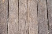 Background texture of dried cracked weathered wooden boards or planks on an outdoor deck