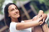 Close up Slim Asian Indian Woman in White Shirt Relaxing Outdoor with Arms Crossing on Knees.