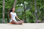 Healthy Young Woman Relaxing at the Beach with Yoga Activity. Captured on White Sand with Green Trees at the Background.
