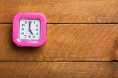 Pink Clock On Wooden Background