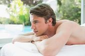 Side view of a handsome young man lying on massage table at spa center