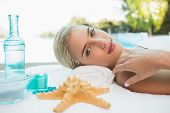 Portrait of a beautiful young woman lying on massage table at spa center