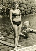 POLAND, CIRCA SIXTIES - Vintage photo of woman in swimsuit with a pedalo in background