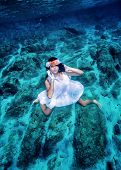 Fashion model underwater, beautiful woman wearing white dress and floral wreath swimming in transparent clear sea, active summer vacation concept