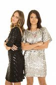 Two Woman In Shiny Dresses Stand Arms Folded