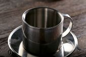 steel cup  and saucer on wood background close-up