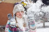 image of snowball-fight  - Portrait of a frowning young woman in the middle of a snowball fight getting a snowball in her face - JPG