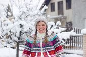 foto of snowball-fight  - Portrait of a happy young woman in the middle of a snowball fight on a snowy winter day - JPG