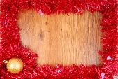 christmas red tinsel frame border on wood surface