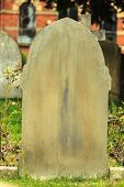 stock photo of graveyard  - Single tombstone and graves in an ancient church graveyard burial ground - JPG