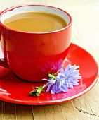 Chicory drink in red cup with flower on saucer