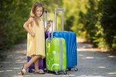 Little girl waiting on the road with suitcases.