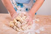 Hands Kneading Dough On Board