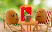 stock photo of flames  - funny eggs on a beach chair relaxing and flaming candle with christmas tree bokeh behind - JPG