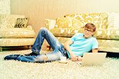 Casual young man lying on the floor with a laptop in the comfort of his home.