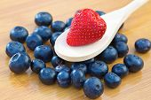Strawberry on a wooden spoon with blueberries