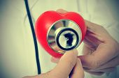 image of auscultation  - a doctor auscultating a red heart with a stethoscope - JPG