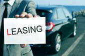 man in suit holding a signboard with the word leasing written in it, with a black car in the background