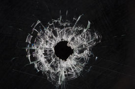 stock photo of gunshot  - bullet holes in glass isolated on black - JPG