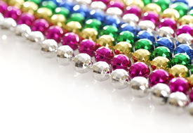 foto of mardi-gras  - rows of colorful mardi gras beads strung out in a line with reflection on white background  - JPG
