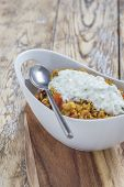 picture of curry chicken  - Bowl with curry flavored rice chicken and vegetables with garlic yoghurt sauce on rustic wooden table