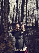 stock photo of bow arrow  - Medieval archer woman she wearing a chainmail and use a bow and arrow gloomy forest cross - JPG