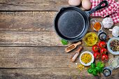 stock photo of pepper  - Ingredients for cooking and cast iron skillet on an old wooden table - JPG