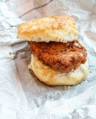picture of southern fried chicken  - A fresh fried piece of chicken on a fluffy biscuit on foil - JPG