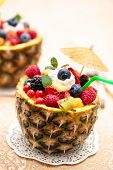 foto of mints  - Fresh fruit salad in pineapple bowl with kiwi, orange, berries and mint leaf (Focus on part of mint leaf and on berries next to it).