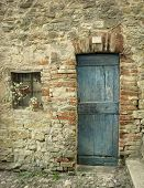 pic of farmhouse  - Detail of an old facade with door and a little window of a farmhouse - JPG