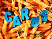 picture of carbohydrate  - Carbs carbohydrates nutrition concept as a plate of cooked pasta with the word for complex sugar imbedded in the starch rich food as a diet and dieting lifestyle concept for healthy portion control - JPG