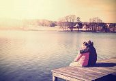 picture of pier a lake  - Retro filtered photo of a couple sitting on pier by lake - JPG