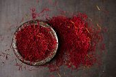 picture of saffron  - saffron spice threads and powder  in vintage iron dish  old metal background - JPG