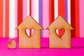 pic of two hearts  - Two wooden houses with hole in the form of heart with little heart on red striped background - JPG