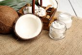 pic of sackcloth  - Coconut with jars of coconut oil and  cosmetic cream on sackcloth background - JPG