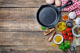 picture of wooden table  - Ingredients for cooking and cast iron skillet on an old wooden table - JPG