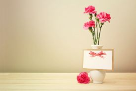 image of carnations  - Pretty Pink Carnation Flowers on White Vase with Blank Greeting Card on Wooden Table with Light Brown Wall Background - JPG
