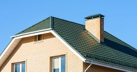 picture of red roof  - chimney on the roof of the house against the blue sky - JPG